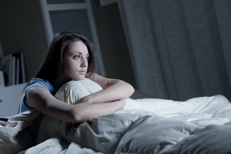 Woman sitting in bed looking anxious at night in semi-darkness.