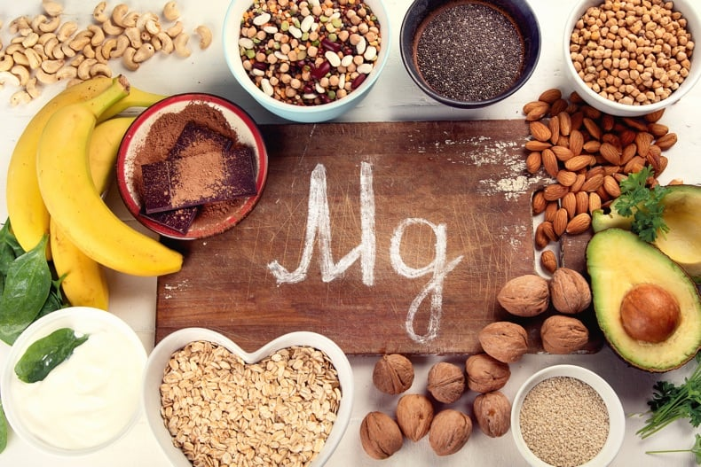 An overhead shot of magnesium-rich foods around a wooden board labeled Mg