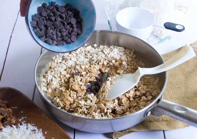 Granola bar ingredients being put together: chocolate chips pouring into dish with oats and nut butter.