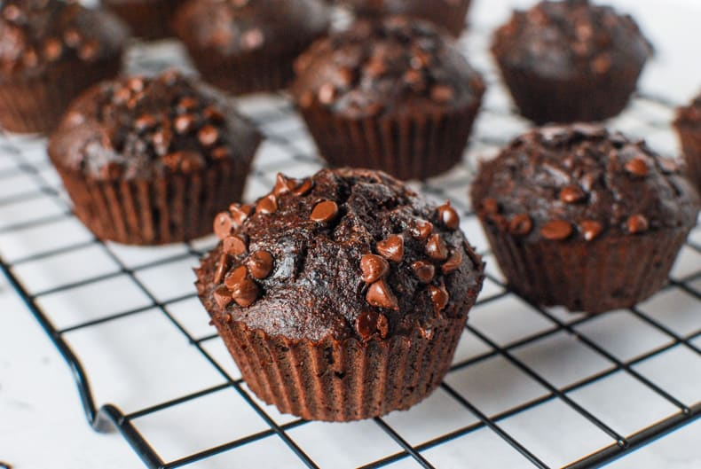 a close up shot of coconut flour chocolate banana muffins on a cooling rack, shot on an angle