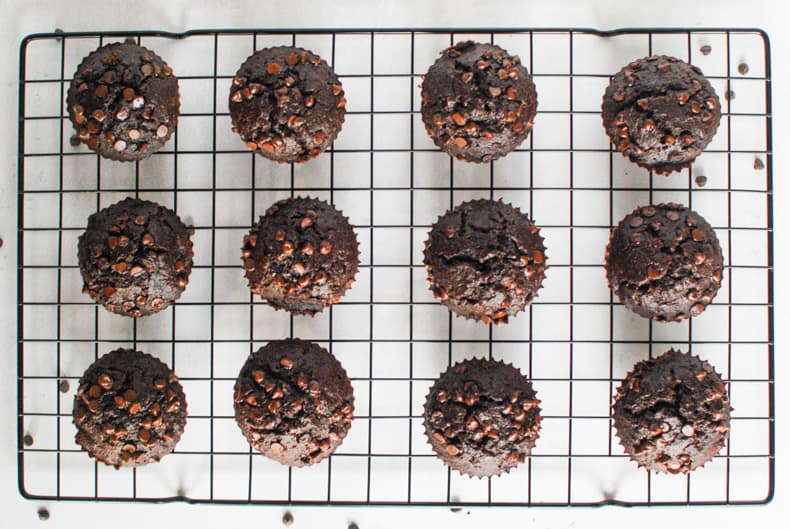 Overhead shot of a dozen coconut flour chocolate muffins on a black cooling rack and white surface,