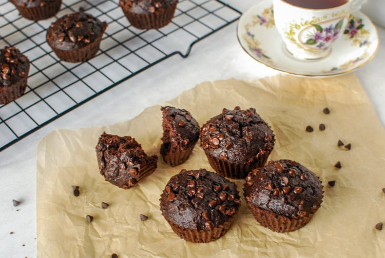 45 degree shot of some coconut flour chocolate muffins on a piece of parchment paper with a cup of tea and muffins on a cooling rack in the background