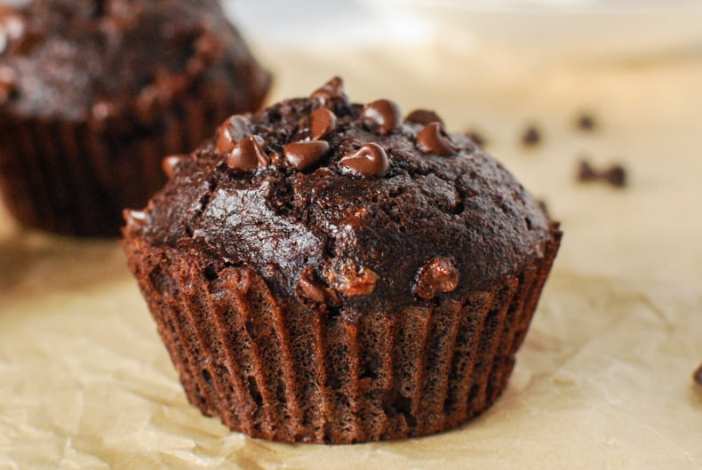 close up shot of coconut flour chocolate muffin with chocolate chips on top, sitting on a parchment paper surface
