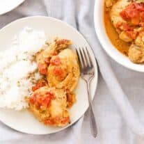 plate of instant pot curry chicken with rice, plus a bowl of chicken for serving, on a grey linen