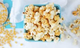 an overhead shot of stovetop kettle corn in a turquoise ceramic basket, with white background