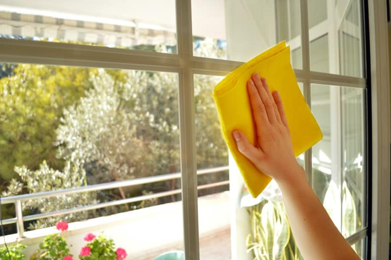 an arm and hand holding a yellow cloth, spring cleaning a window from inside an apartment