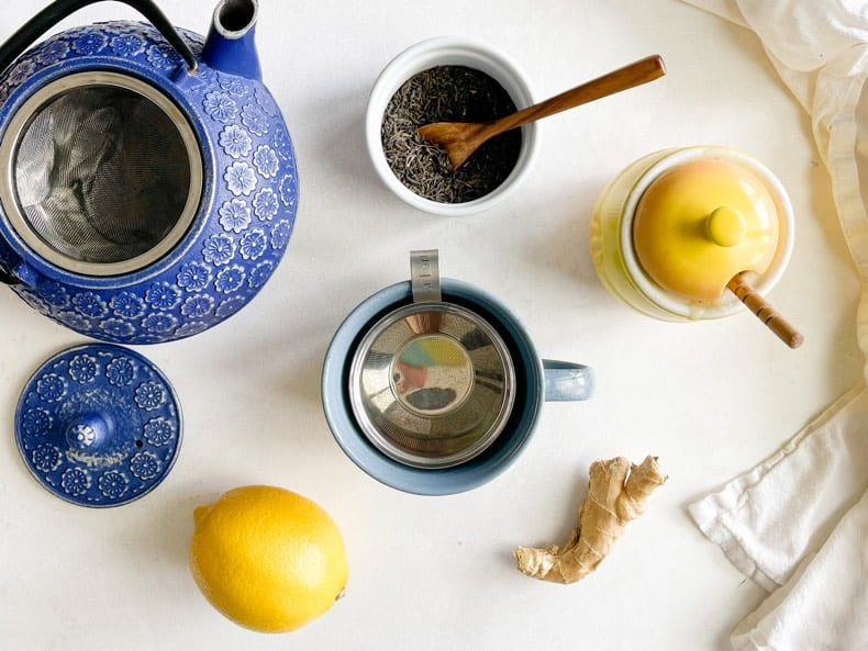 Ingredients for stomach debloating tea remedy on a white surface, including a mug in the center, fresh ginger, fresh lemon, honey, loose green tea, and a blue cast iron teapot