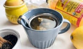 a blue mug with debloating tea with apple cider vinegar, lemon, ginger, and green tea.