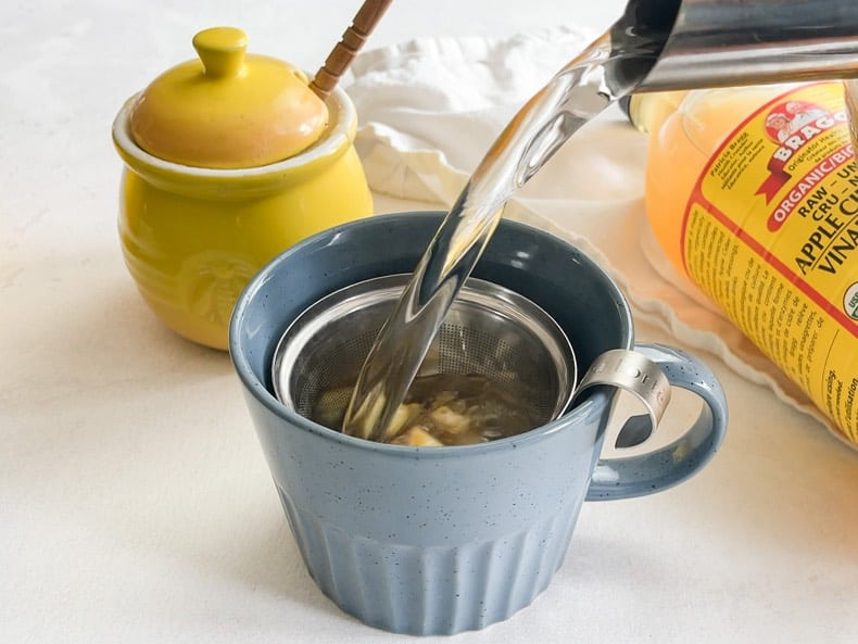 Pouring water from the kettle into a blue mug with minced fresh ginger to make debloating tea remedy