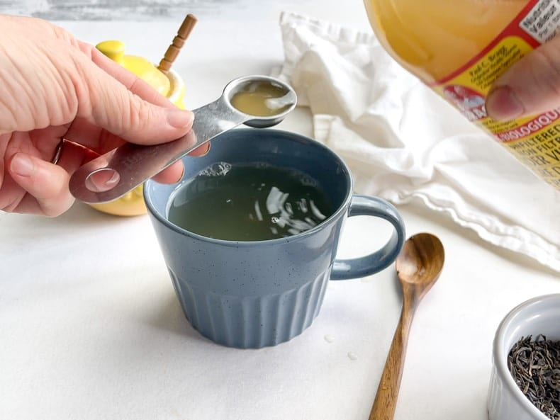 adding a teaspoon of apple cider vinegar to a mug of tea remedy made with ginger and green tea and lemon