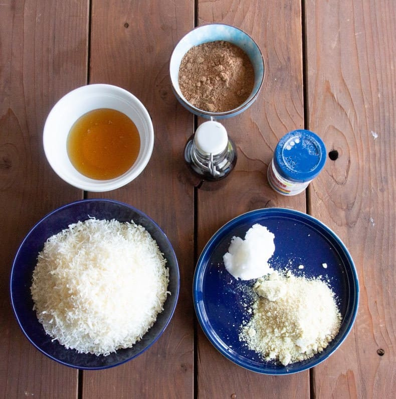 Ingredients for chocolate coconut macaroons laid out on a wooden table: coconut flakes, coconut oil, almond meal, vanilla, honey, cocoa, and salt.