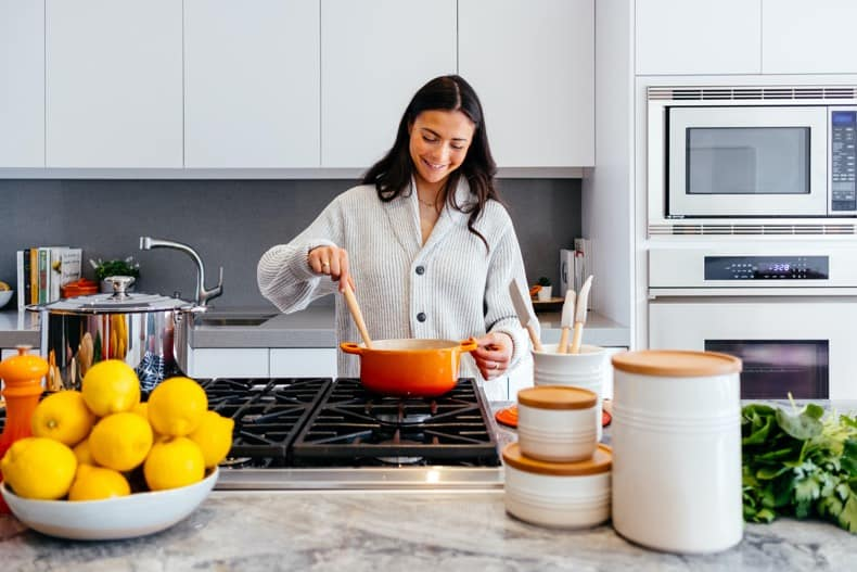 woman cooking a quick and easy meal with an orange pot, with a white kitchen