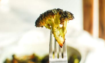 A perfectly crispy piece of air fryer broccoli held up on a fork.