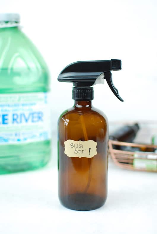 vertical image of a brown glass spray bottle of DIY mosquito repellent with distilled water and essential oils in the background