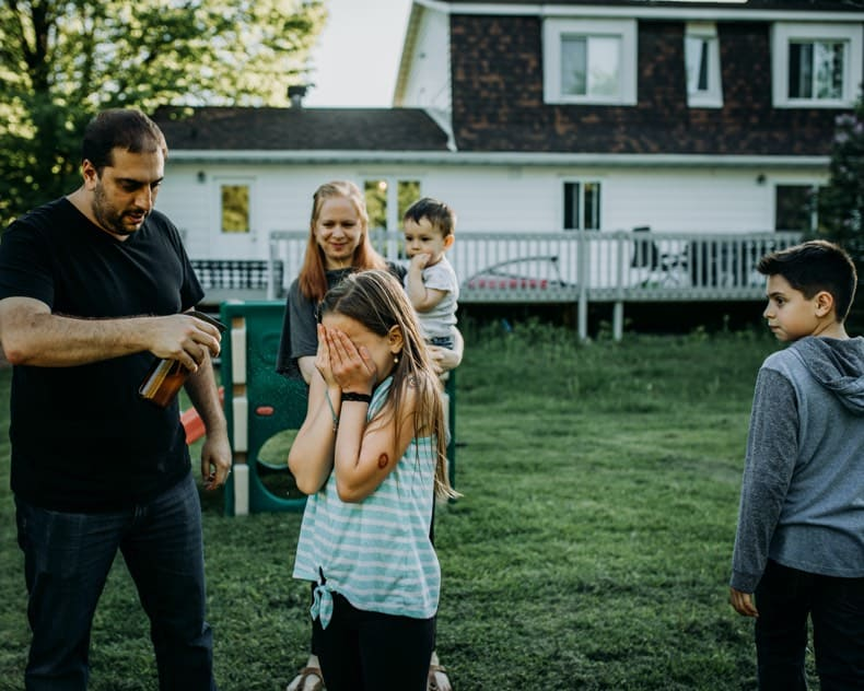 family standing together outside while dad sprays homemade diy mosquito repellent on the daughter in a grassy backyard with house in background